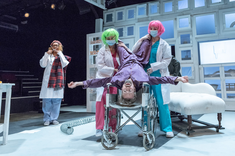 Erik Hoover as Argan the hypochondriac upside down in a wheelchair