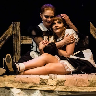 """Christine (Kayla Dvorak Feld) and Lea (Nissa Nordland Morgan) cuddle in their new room in Theatre Pro Rata's production of """"My Sister in This House"""""""