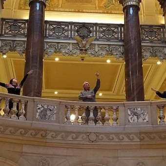 Three actors standing in the rotunda of the Minnesota State Capitol Building