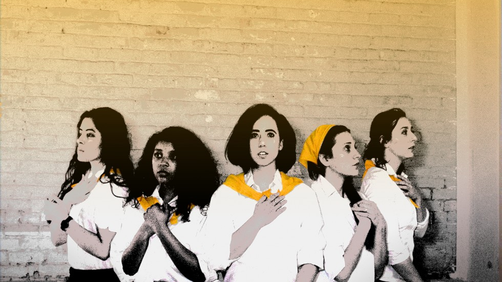 5 sisters wearing matching yellow scarves gather to show reverence against a brick wall.