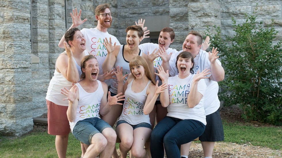 "Exuberant group of eight standing in front of a stone church building with their hands raised excitedly, all wearing matching t-shirts with the words ""CAMP, CAMP, CAMP"" colored in rainbow."