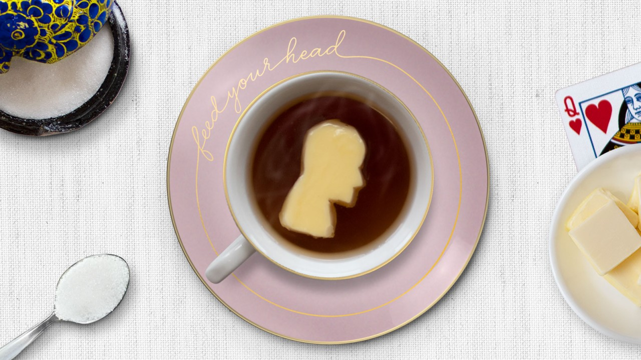 """A tea cup sits on a pink saucer that has the words """"feed your head"""" engraved in gold script. The cup is filled with steaming hot tea.  A pat of butter carved into a profile of a person's head floats in the tea. Surrounding the cup and saucer are: a silver spoon filled with sugar; an ornate, blue and black, sugar bowl with its lid ajar; a small white saucer holding square pats of butter, and Queen of Hearts playing card. This all sits on a white linen tablecloth."""