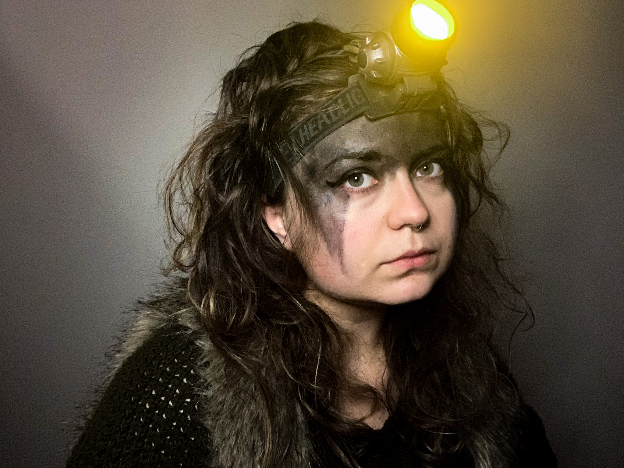Zoë Rose, dressed in warm clothes and a headlamp, with coal dust smeared decoratively across her face, eyes the camera warily as Mel in the online revival of Electric Sun.